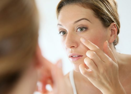 Woman examining her wrinkles in the mirror
